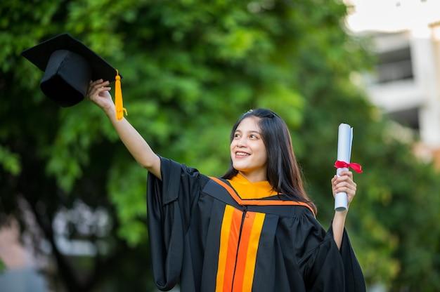 Portrait female graduate university graduate holding a black hat