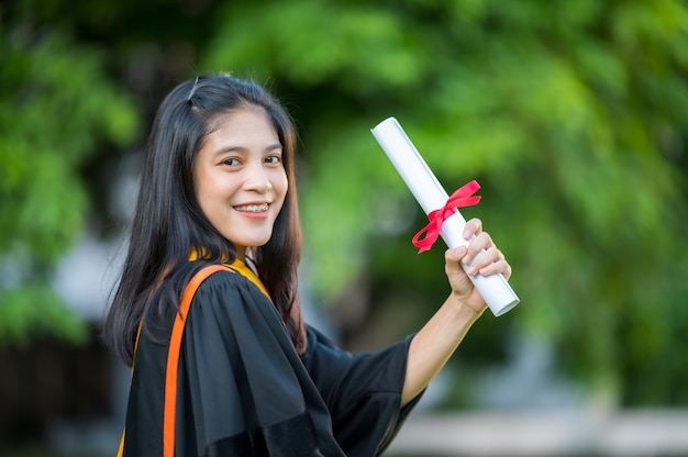 Portrait a female graduate with a university degree holding a diploma and having fun