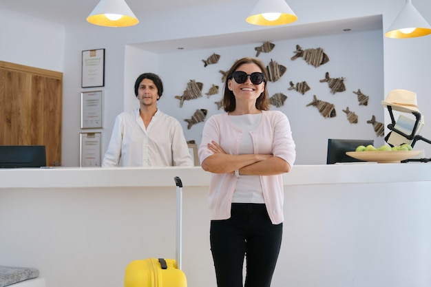 Portrait of female guest with suitcase, male hotel worker near reception