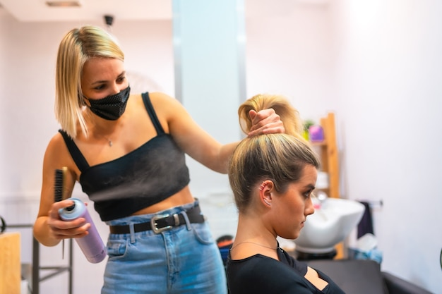 Portrait of a female hairdresser in a medical mask doing her job new normal