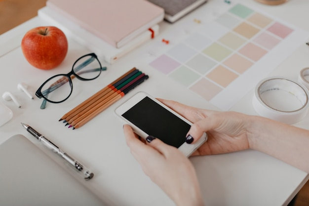 Portrait of female hands with phone, apple, glasses, scotch and other stationery on white.