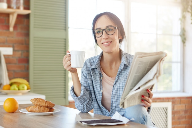 Portrait of female has breakfast, drinks coffee or tea with croissants and chocolate, reads newspaper alone at home.