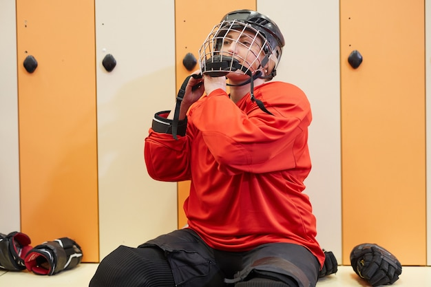 Portrait of female hockey player putting on helmet in locker room