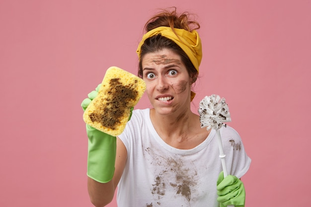 Portrait of female housekeeper with annoyed expression while doing house cleaning demonstrating dirty sponge and brush wearing protective rubber gloves. angry young female hating doing house work