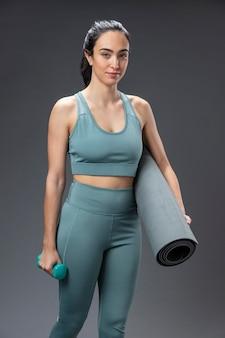 Портрет женщины в спортивной одежде, держащей коврик