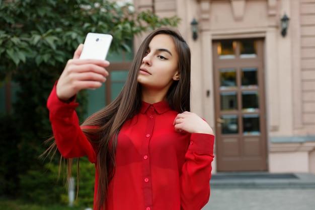 셀카를 만드는 세련된 의상을 입은 여성 초상화. 목적지 도시를 방문하는 아름다운 젊은 여성의 초상화, 휴대전화를 사용하여 셀카 비디오로 자신을 촬영하고, 손을 흔들고, 카메라를 보며 웃고 있습니다.