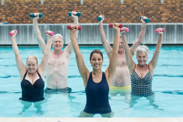 Portrait of female instructor with senior swimmers exercising in swimming pool
