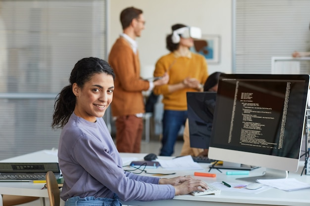 Portrait of female it developer looking at camera and smiling while using computer with code on screen in software production studio, copy space