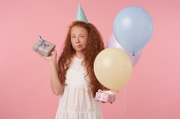 Ritratto di bambino femmina con capelli lunghi foxy che indossa abiti festivi celebra la festa, in piedi con scatole regalo in mani su sfondo rosa bambini e concetto di celebrazione