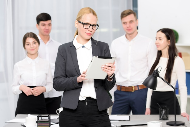 Portrait of a female manager holding digital tablet in hand standing in front of colleague