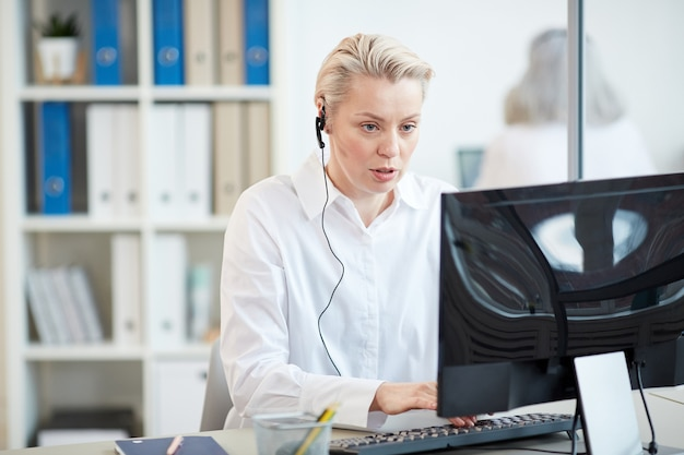 Portrait of female manager wearing headset and using computer while answering customer service request in office interior