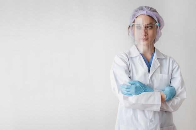 Portrait of female medical doctor wearing face shield for protect coronavirus with arms cross