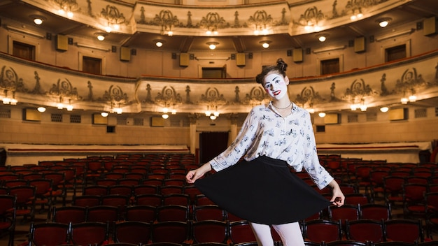 Portrait of female mime standing in an auditorium posing