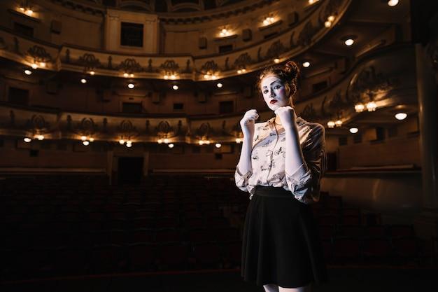 Portrait of female mime standing in auditorium