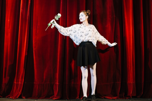 Portrait of female mime standing in front of red curtain holding white rose