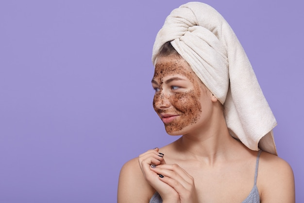 Portrait of female model applies chocolate mask on face, has positive expression, looks aside
