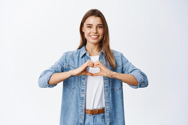 Il ritratto del modello femminile con i capelli biondi e il sorriso bianco ama qualcosa, mostrando il gesto del cuore e sorridendo per esprimere simpatia, parete dello studio