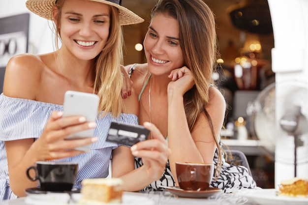 Portrait of female models make shopping online, use smart phone, credit card, sit together at cafe interior with aromatic coffee, have positive looks. best friends recreat together, uses technologies