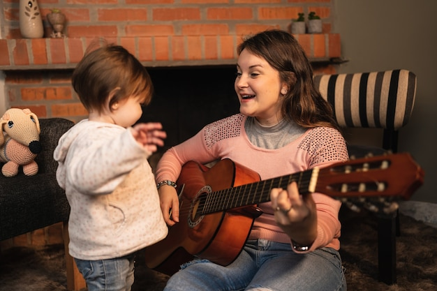 Portrait of female musician plays guitar with her daughter.