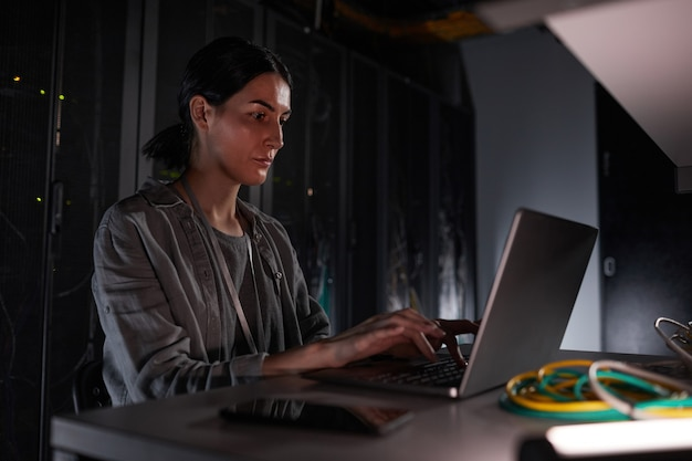 Portrait of female network engineer using laptop while sitting in dark server room, copy space