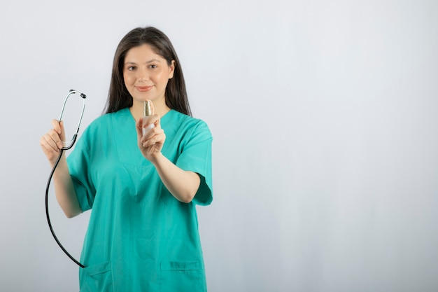 Portrait of female nurse holding stethoscope on white.