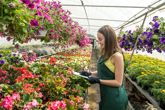Portrait of female nursery at work in greenhouse, holding clipboard and checks the condition of plants