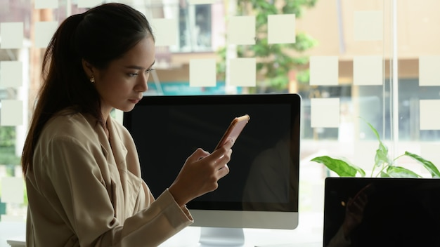 Portrait of female office worker using smartphone while sitting at office table with digital devices in office room
