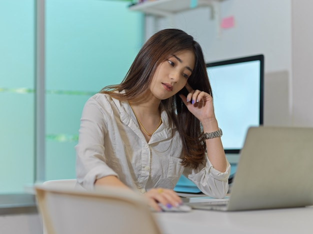 Portrait of female office worker work from home with laptop and computer in home office room