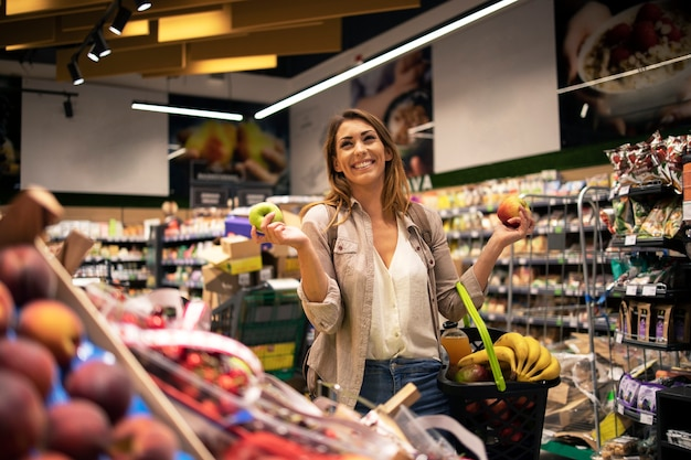 Portrait of female person in supermarket holding fruit and smiling