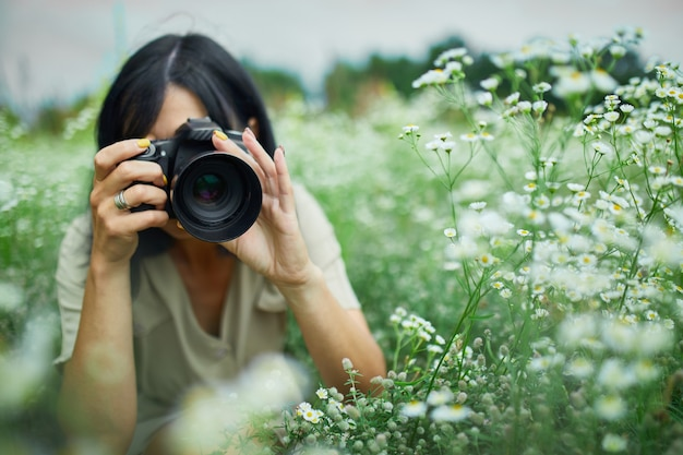 Portrait of female photographer take photo outdoors on flower field landscape holding a camera, woman hold digital camera in her hands. travel nature photography, space for text, top view.
