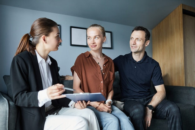 Portrait of female real estate agent signing contract with young couple buying new house, copy space