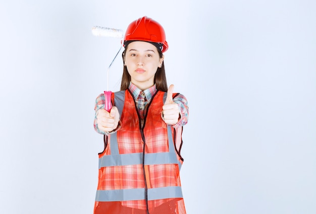 Portrait of female repairer in uniform holding painting roller over white wall.