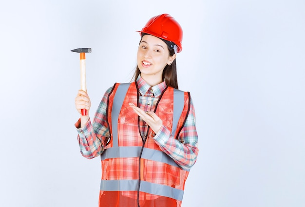 Portrait of female repairer in uniform standing with hammer over white wall.