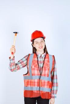 Ritratto di riparatore femminile in uniforme in piedi con martello sul muro bianco.