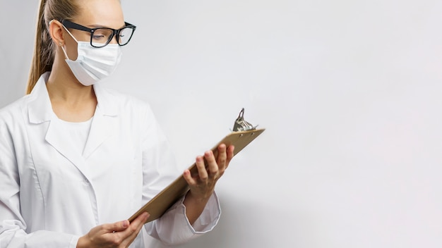 Portrait of female researcher in the lab with medical mask and clipboard