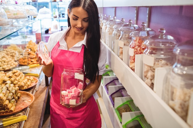 Ritratto di donna negoziante tenendo un barattolo di dolci turchi al bancone