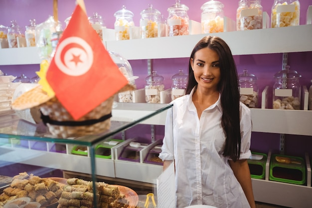 Portrait of female shopkeeper standing at turkish sweets counter