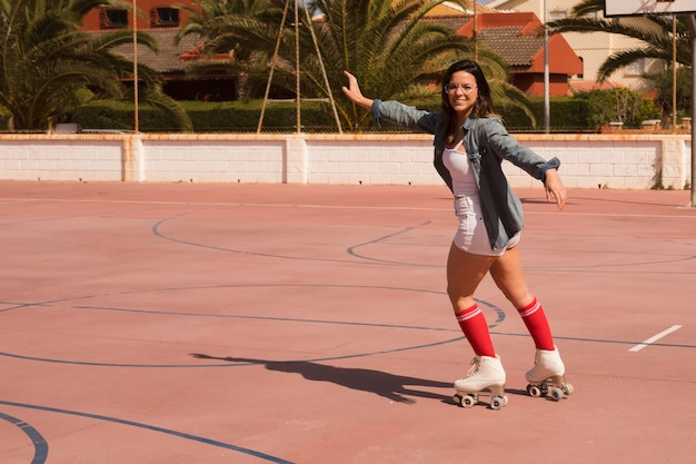 Portrait of a female skater outstretching her arms skating on an outdoor court