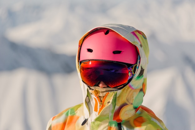 Portrait of female snowboarder in pink sports helmet and bright colorful sportswear