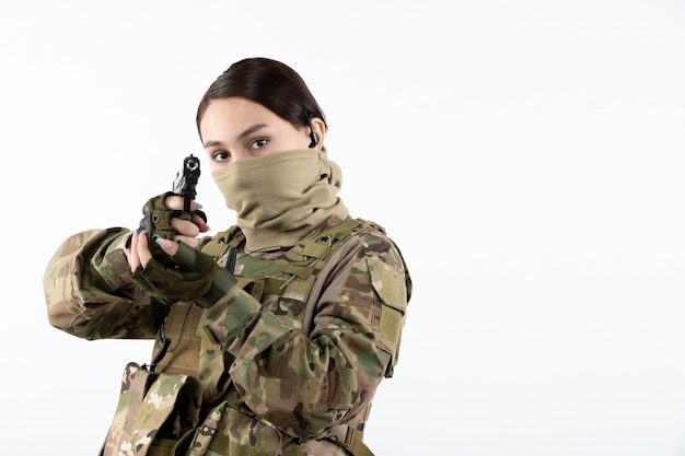Portrait of female soldier with gun in camouflage white wall