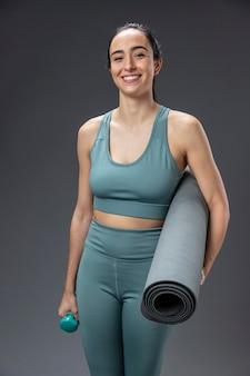 Ritratto femminile in abbigliamento sportivo tenendo la stuoia