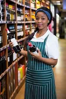 Portrait of female staff arranging wine bottles on shelf