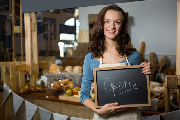 Portrait of a female staff holding a open sign