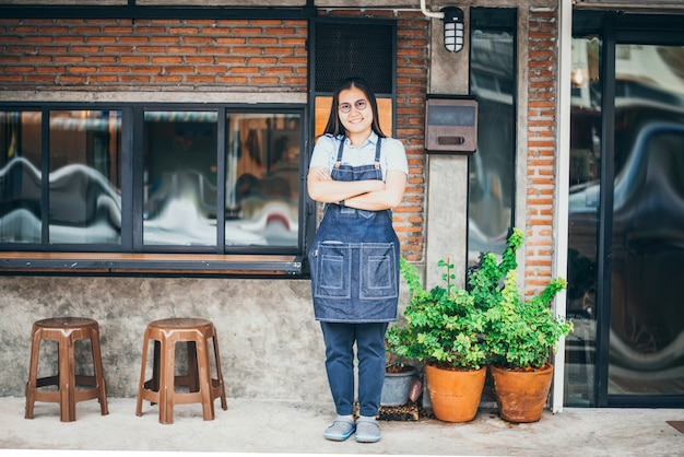 Portrait of female standing in front of coffee shop, small busin