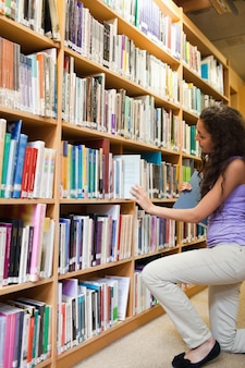 Portrait of a female student choosing a book