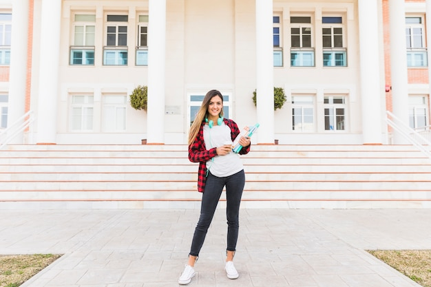 Portrait of a female student holding books in hand standing in front of college