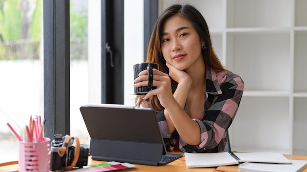 Portrait of female student smiling to camera while drinking coffee break while doing assignment in living room