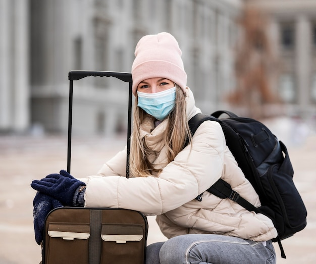 Portrait female student wearing mask and carrying luggage