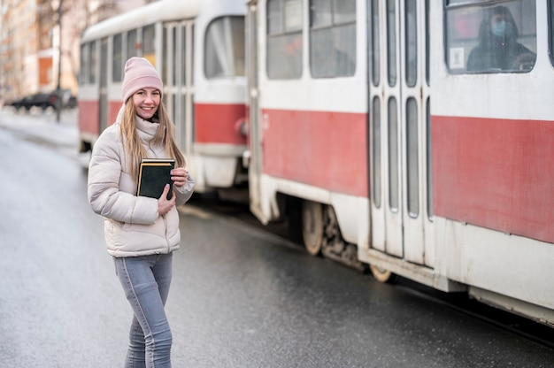 Portrait female student with books at tram stop