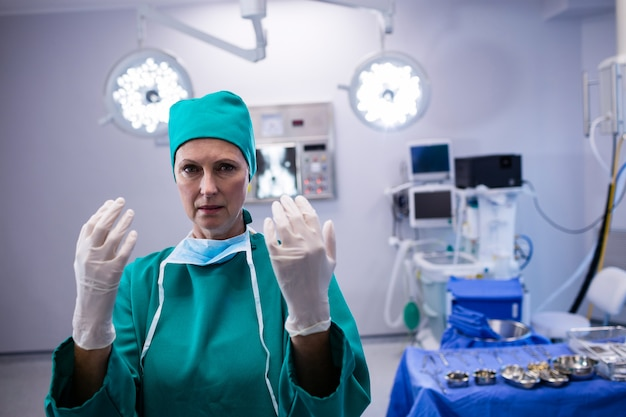 Portrait of female surgeon wearing surgical gloves in operation theater